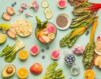 Disposizione piana degli ingredienti alimentari sani con la vari frutta, verdure, semi e dado sul fondo leggero della menta Misce immagini stock