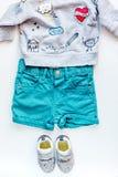 Disposizione piana dei bambini con la vista superiore del fondo bianco dei vestiti Immagine Stock Libera da Diritti