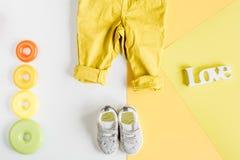 Disposizione piana dei bambini con la vista superiore del fondo giallo dei vestiti Immagine Stock Libera da Diritti