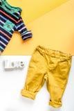 Disposizione piana dei bambini con lo spazio giallo di vista superiore del fondo dei vestiti per testo Immagine Stock