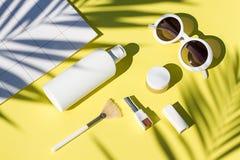 Disposizione piana dei cosmetici gialli di estate con gli occhiali da sole Bellezza di vista superiore Fotografia Stock