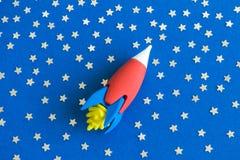 Disposizione piana del giocattolo del razzo nello spazio con le stelle astratte immagine stock libera da diritti