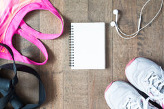 Disposizione piana del taccuino vuoto, reggiseno rosa di sport di colore, equipmen di sport Fotografia Stock