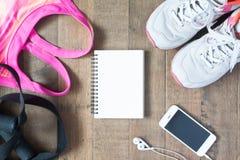 Disposizione piana del taccuino vuoto, reggiseno rosa di sport di colore, equipmen di sport Fotografia Stock Libera da Diritti