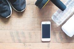 Disposizione piana del telefono cellulare con le attrezzature di sport su fondo di legno Scarpa da tennis della donna con l'attre Fotografie Stock
