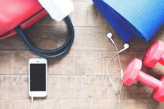 Disposizione piana del telefono cellulare con le cuffie e le attrezzature di sport su fondo di legno Immagini Stock Libere da Diritti