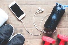 Disposizione piana del telefono cellulare con le cuffie e le attrezzature di sport su fondo di legno Allenamento e forma fisica Immagine Stock