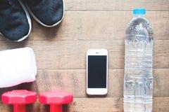 Disposizione piana del telefono cellulare, della bottiglia di acqua, dell'asciugamano e delle teste di legno rosse su legno Fotografia Stock Libera da Diritti