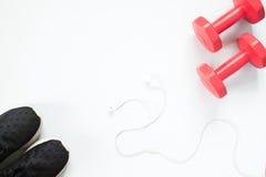 Disposizione piana del trasduttore auricolare, delle teste di legno rosse e delle attrezzature di sport su bianco Immagine Stock Libera da Diritti