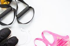 Disposizione piana del trasduttore auricolare, delle teste di legno rosse e delle attrezzature di sport su bianco Fotografia Stock