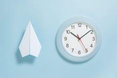 Disposizione piana dell'aereo del Libro Bianco e dell'orologio di parete sul fondo blu pastello di colore Immagini Stock