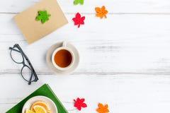 Disposizione piana dell'area di lavoro femminile dello scrittorio con il diario, gli occhiali, il libro, la tazza del tè, i dolci Immagini Stock