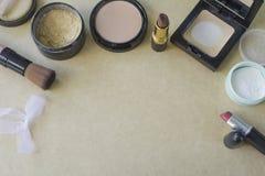 Disposizione piana dell'insieme dei cosmetici per trucco su carta marrone Fotografie Stock
