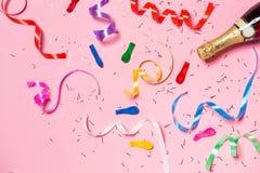 Disposizione piana della celebrazione Bottiglia di Champagne con la st variopinta del partito Fotografia Stock Libera da Diritti