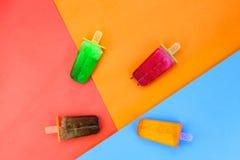 Disposizione piana della crema del gelato alla frutta dell'insieme su fondo di carta variopinto, ghiaccio Fotografia Stock