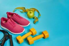 Disposizione piana della testa di legno, della bottiglia di acqua, della corda di salto e della scarpa da tennis, attrezzature di Fotografie Stock