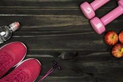 Disposizione piana delle scarpe rosse di sport, teste di legno, cuffie, bottiglia di wat fotografie stock libere da diritti
