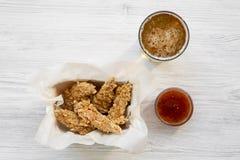Disposizione piana delle strisce del pollo con salsa e birra fredda su una tavola di legno bianca ambientale fotografie stock