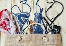 Disposizione piana di modo di estate con il costume da bagno blu del bikini dentro la borsa ed altri accessori della ragazza su f Immagini Stock Libere da Diritti