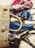 Disposizione piana di modo di estate con il costume da bagno blu del bikini dentro la borsa ed altri accessori della ragazza su f Fotografie Stock