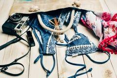 Disposizione piana di modo di estate con il costume da bagno blu del bikini dentro la borsa ed altri accessori della ragazza su f Immagini Stock