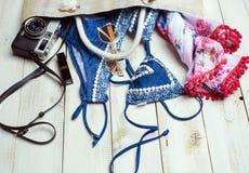 Disposizione piana di modo di estate con il costume da bagno blu del bikini dentro la borsa ed altri accessori della ragazza su f Immagine Stock Libera da Diritti
