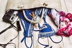 Disposizione piana di modo di estate con il costume da bagno blu del bikini dentro la borsa ed altri accessori della ragazza su f Fotografia Stock