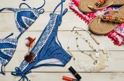 Disposizione piana di modo di estate con il costume da bagno blu del bikini e gli accessori della ragazza su fondo di legno bianc Fotografia Stock