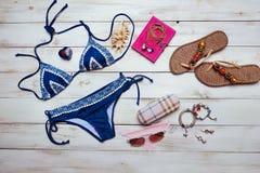 Disposizione piana di modo di estate con il costume da bagno blu del bikini e gli accessori della ragazza su fondo di legno bianc Fotografia Stock Libera da Diritti