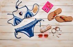 Disposizione piana di modo di estate con il costume da bagno blu del bikini e gli accessori della ragazza su fondo di legno bianc Immagine Stock Libera da Diritti