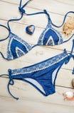 Disposizione piana di modo di estate con il costume da bagno blu del bikini e gli accessori della ragazza su fondo di legno bianc Fotografie Stock Libere da Diritti