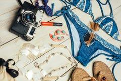 Disposizione piana di modo di estate con il costume da bagno blu del bikini, la macchina fotografica ed altri accessori della rag Fotografia Stock