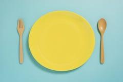 Disposizione piana di stoviglie, del piatto giallo e della forcella sul colo blu pastello Fotografia Stock
