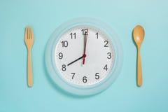 Disposizione piana di tempo del pasto, del cucchiaio dell'orologio di parete e della forchetta sul blu pastello Immagini Stock