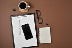 Disposizione piana, scrittorio della tavola dell'ufficio di vista superiore Area di lavoro con il bordo di clip in bianco, taccui fotografia stock