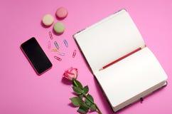 Disposizione piana, scrittorio della tavola dell'ufficio di vista superiore area di lavoro femminile dello scrittorio con le rose Immagine Stock