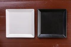Disposizione piana sopra i piatti quadrati in bianco e nero sulla tavola dei bordi di legno Fotografie Stock