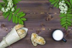 Disposizione piana Sulla tavola, sui fiori della molla, su una tazza di latte e sui biscotti casalinghi dolci fotografie stock