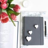 Disposizione piana: Tulipano rosso, petali rossi e una bibbia su una tavola bianca fotografie stock libere da diritti