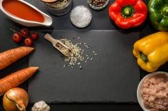 Disposizione piana, vista superiore Fine in su Ingredienti per cuocere i peperoni dolci farciti allineati intorno ad un tagliere  immagine stock libera da diritti
