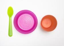 Disposizione variopinta del cucchiaio, della ciotola e della tazza plactic per l'isolante del bambino Immagini Stock