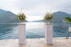 Disposizioni dei fiori sui supporti per una cerimonia di nozze sul pilastro contro il mare fotografia stock libera da diritti