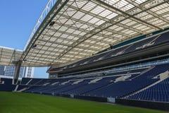 Disposizioni dei posti a sedere blu, banchi verdi del passo, della galleria e di vetro dentro lo stadio vuoto prima della partita Immagini Stock