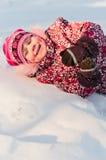 Disposizioni del bambino su neve e sulla risata Fotografia Stock