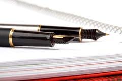 Disposizioni delle penne di fontana su un scrittura-libro Fotografia Stock
