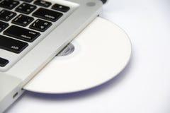 Disque blanc de Cd ou de dvd dans l'ordinateur portatif Images libres de droits