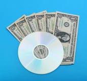 Disque de DVD avec des notes du dollar Image libre de droits