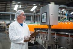 Disque de maintien d'ingénieur d'usine sur le presse-papiers dans l'usine Photographie stock