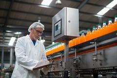 Disque de maintien d'ingénieur d'usine sur le presse-papiers dans l'usine Image libre de droits