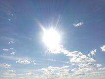 Disque solaire, lumière lumineuse, rayons de soleil, petits nuages, ciel bleu, lumière pure, rayons d'or Photo libre de droits